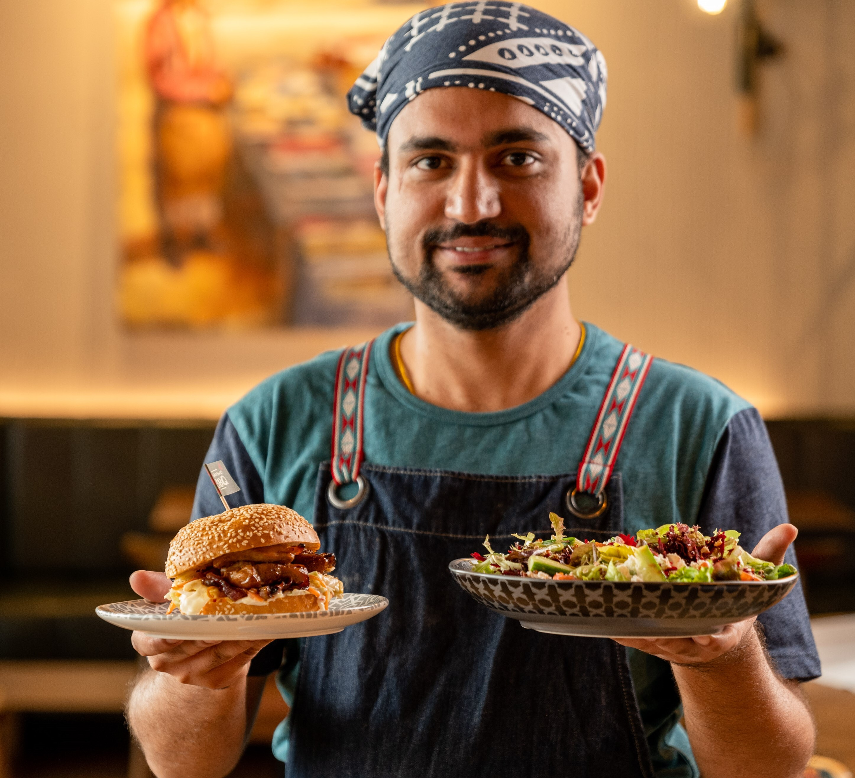 A Nando's staff member carrying a burger and a salad